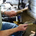 13. Using a heavy planishing hammer on the neck on a curved stake.