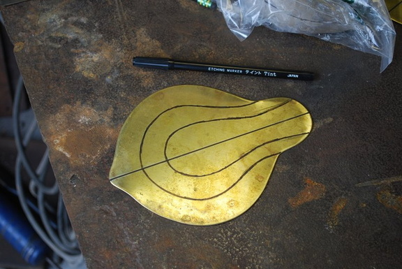 8. The brass piece has been cut out, annealed and pickled, and lines drawn on it as guides for hammering.