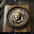 13. By partially melting the wax on both surfaces, the face is adhered to a wax base.
