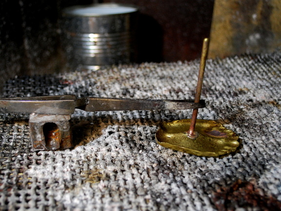29. A brass rod silver-soldered to the feet. it will fit tightly into a hole drilled in the wood.