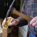 16. Hammering on a wood block to even out the ripples.