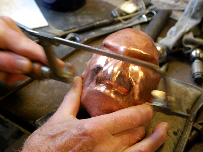 17. Cutting open the mouth with a jeweler's saw. After all, this is to be a teapot, so it has to have a spout.