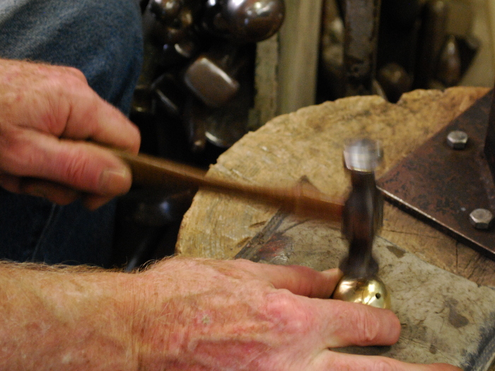 57. Using a planishing hammer, pushing in the bulges to make it more spherical.